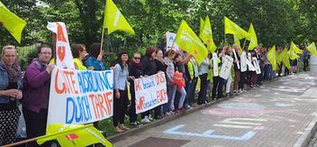 Auszubildende des Klinikums Chemnitz stehen in einer Reihe und zeigen ihre Vorderungen auf Transparenten und Fahnen.