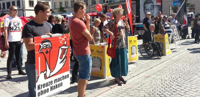 Menschen stehen in einer breiten Front den Nazis gegenüber und halten Plakate und Transparente gegen Rassismus und gegen die NPD in der Hand