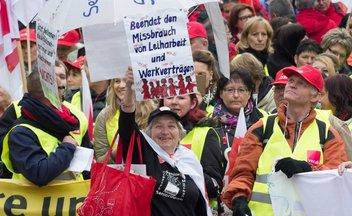 Seniorin in der Menge mit Schild Beendet den Missbrauch von Leiharbeit und Werkverträgen