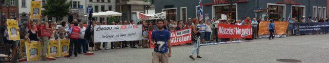 Sehr viele Menschen stehen in einer Reihe und halten verschiedenen Transparente und Schilder mit Parolen gegen Nazis hoch.