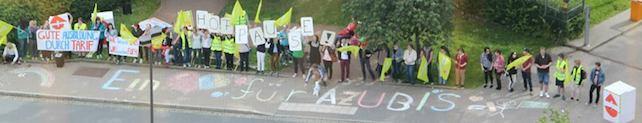 """Die Kundgebung von oben. Auszubildende stehen in einer Reihe mit Fahnen und Transparenten. Auf dem Gehweg steht mit Kreide der spruch: """"Ein Hertz für Azubis."""""""