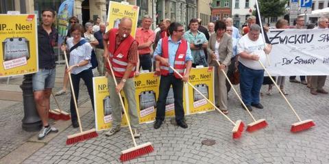 Menschen Kehren mit roten Besen symbolisch die NPD aus der Stadt.