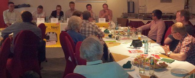 Ein Saal mit vielen Menschen, die mit Kandidatinnen und Kandidaten zur Landtagswahl diskutieren.