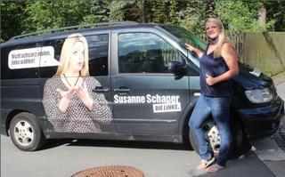 Susanne Schaper steht vor einem Kleinbus der mit Wahlwerbung von ihr beklebt ist.