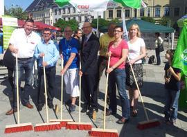 Menschen kehren mit roten Besen symbolisch die NAzis aus der Stadt