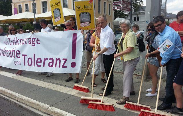 Menschen fegen mit Besen symbolisch die Nazis aus der Stadt