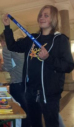 Ein Jugendlicher hält ein Schlüsselband mit dem Spruch: Kein Sex mit Nazis! hoch.