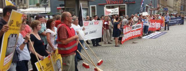 Viele Menschen die den Nazis gegenüberstehen und mit Pfeifen und Transparenten ihren Protest ausdrücken.