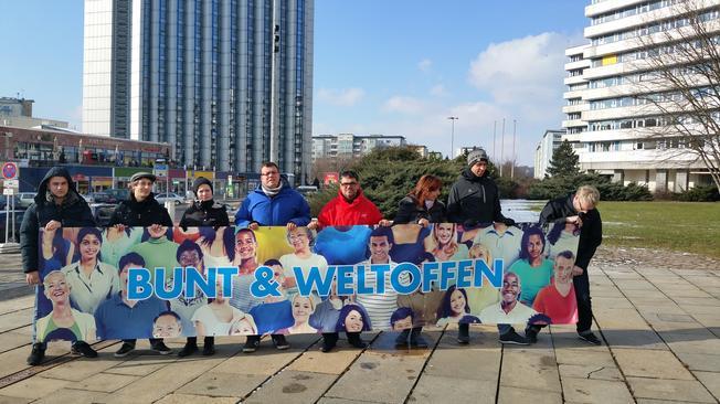fünf menschen halten ein Transparent auf dem steht: Bunt und Weltoffen