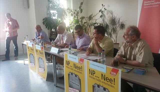 Die Teilnehmer der Podiumsdiskussion sitzen auf dem Podium wärend Bernd Rudolph die Anwesenden begrüßt