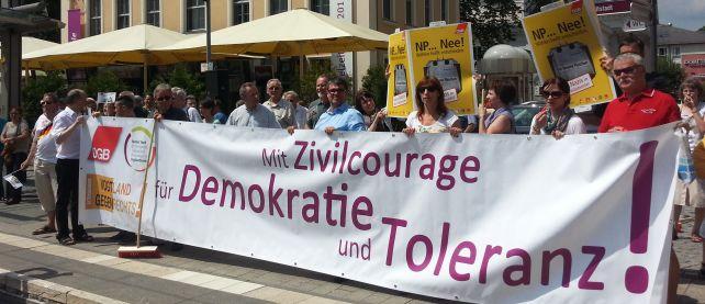 """Menschen halten ein Transparent mit der Aufschrift: """"Mit Zivilcourage für Demokratie und Tolleranz"""""""