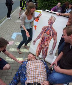 Jugendliche simulieren einen Notfall. Zwei Auszubildende kümmern sich um einen vermeintlich Verletzten.