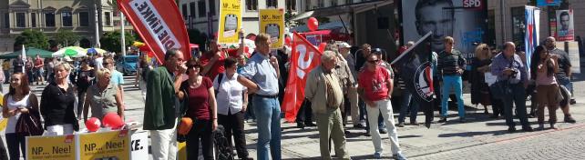 Viele Menschen stehen nebeneinander und halten Schilder und Transparente gegen die NPD hoch