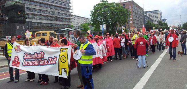 """Viele Mensche formieren sich zu einem Demonstrationszug. Am Anfang ist des Fronttransparent mit der Aufschrift: """"Sauberkeit brauch Sicherheit"""" zu sehen"""