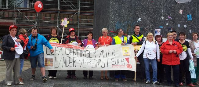 """Menschen halten ein Transparent mit der Aufschrift: """"Gebäudereiniger aller Länder vereinigt euch!"""""""