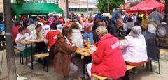 Viele Menschen essen an Bierbänken und Tischen im Freien.