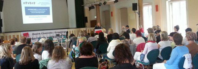 Viele Menschen sitzen in einem Saal und hören einer Referentin zu.